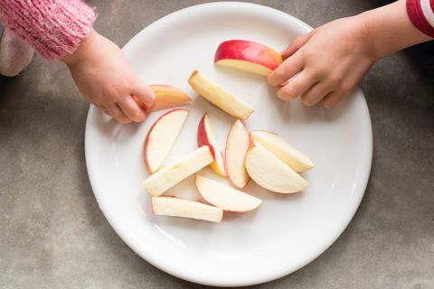 Цроппед Hands Of Children Having Apple At Home